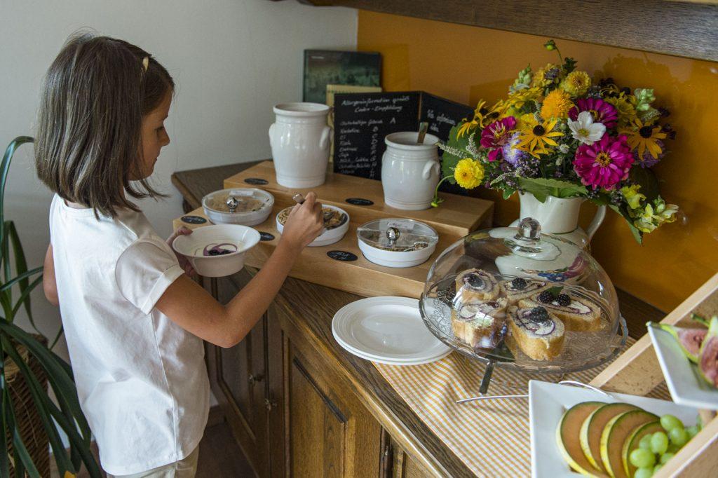 Kind bedient sich am Frühstücksbuffet – Privatzimmer Haring