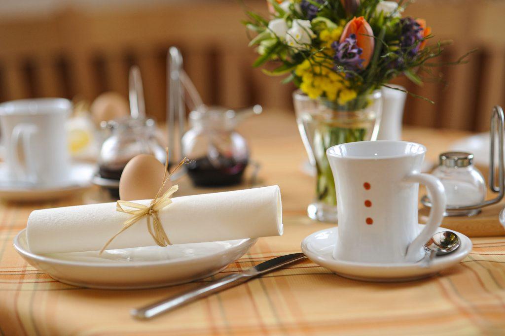 Früstückstisch gedeckt mit Ei und Blumen – Privatzimmer Haring