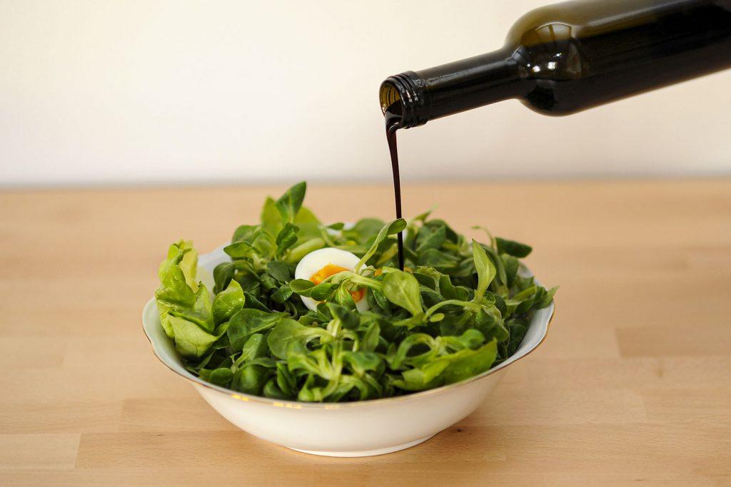 Kernöl wird auf Salat geschüttet