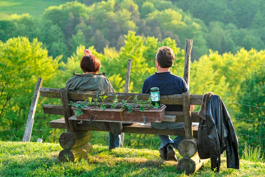 Zwei Personen sitzen auf einer Bank in der Natur